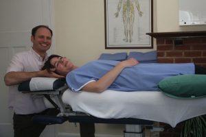 Chiropractor Raising Patients Head
