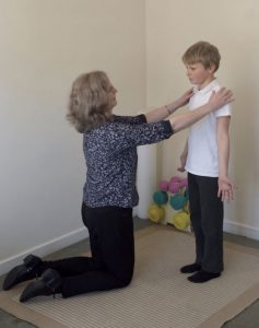 Michelle Helping To Correct Posture Of Child